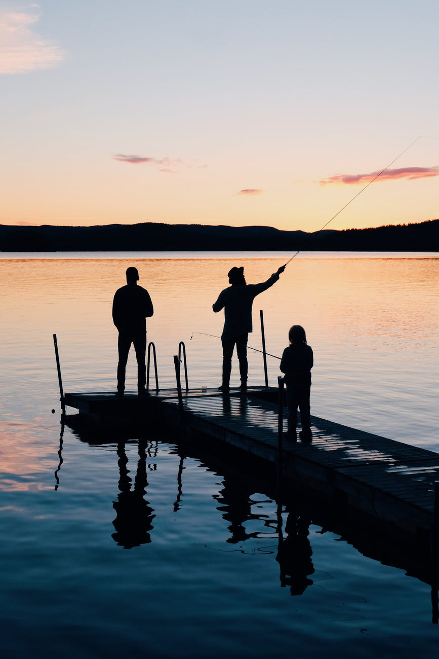 three people on a wooden fishing docks