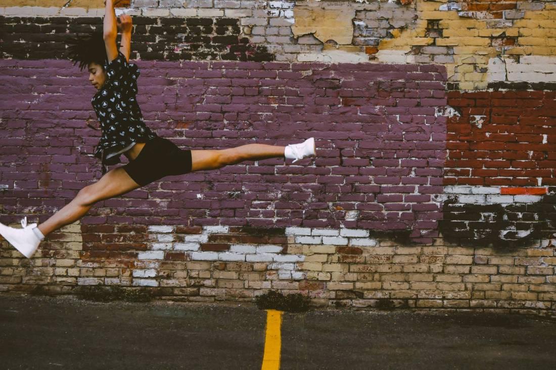 photo of person jumping near brick walls