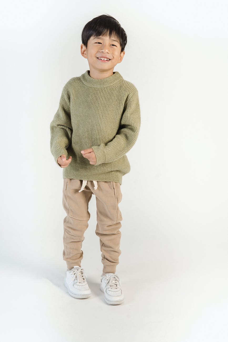 boy in green sweater and brown pants